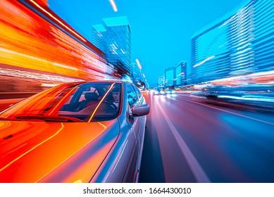 Blick von der Vorderseite des Autos, das sich in einer Nachtstadt bewegt, verwischte Straße mit Lichtern mit Auto auf hoher Geschwindigkeit.