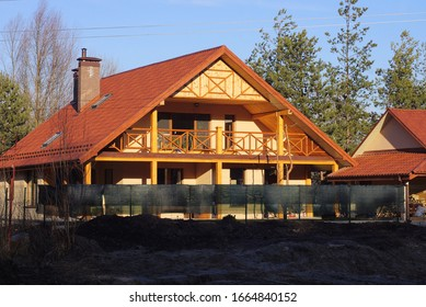 facade of a brown private house with a wooden balcony under a red tiled roof behind a green fence against a blue sky on a sunny day