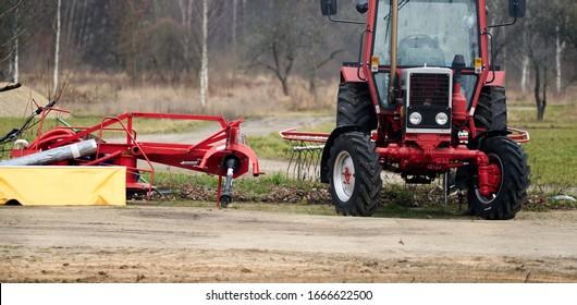 Kleine Landwirtschaft mit Traktor und Pflug auf dem Feld.
