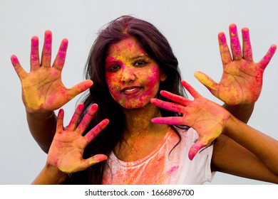 Indian girl showing her colourful hands printing or playing holi festival with colours, isolated white background.Young girl plays with colors on the occasion of Holi.Concept for Indian festival Holi.