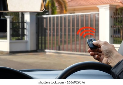 Man in car, hand using remote control to open the automatic gate. The auto electric door, home gate garage remote control and security system  concept.