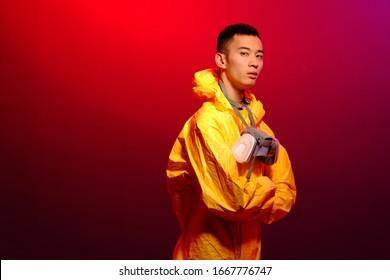 Aziatische man in een geel pak van chemische bescherming en in een beschermend masker op een gekleurde trendy achtergrond. Concept Breaking Bad. Het concept van de verspreide epidemie van het coronavirus vanuit China