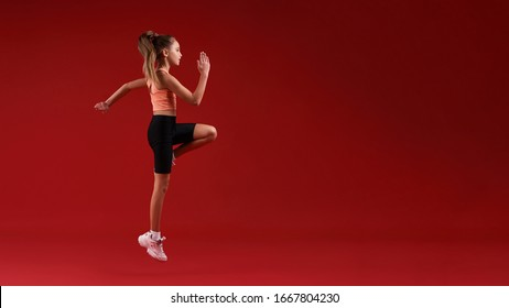 A cute kid, girl is engaged in sport, she is looking away while jumping. Isolated on red background. Fitness, training, active lifestyle concept. Horizontal shot. Side view. Web Banner