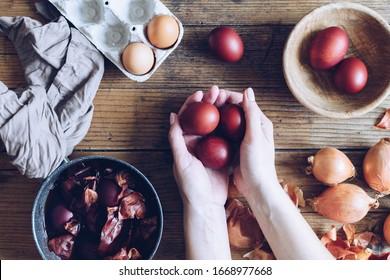 Frau, die gefärbte Ostereier gemalt mit natürlichem Farbzwiebel auf hölzernem Hintergrund malt. Verfahren zum Färben von Eiern mit natürlichen Farben für Ostern. Natürliche ökologische Färbung mit Lebensmittelfarbe. Draufsicht.