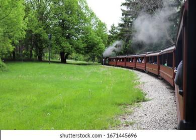 緑の芝生を横切って走っている煙突からの煙のパフを備えた小さな蒸気機関車