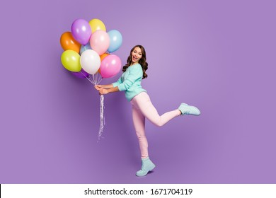 Full body photo of cheerful feminine girl hold many baloons enjoy festive woman day event scream wear turquoise pastel sweater pink footwear isolated over purple color background