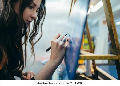Nahaufnahmeporträt der schönen und authentischen jungen Künstlerin oder Malerin schaffen Kunstwerk. Detaillierte Arbeit für persönliches kreatives Projekt. Tätowierer zeichnet Kunstwerk