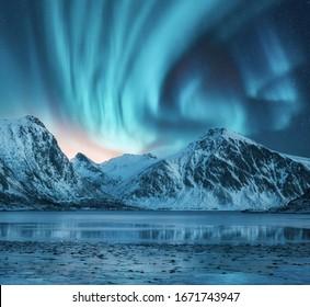 Nordlichter über den schneebedeckten Bergen, der Küste des Sees und Spiegelung im Wasser. Aurora borealis und schneebedeckte Felsen. Winterlandschaft mit Polarlichtern, Fjord. Sternenhimmel mit heller Aurora