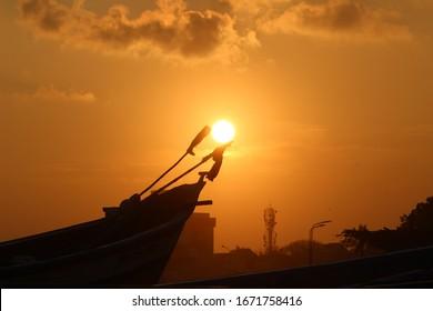 夕日と雲とビーチで1つの画像のボート。ボートの旗の間に沈む夕日と完璧なタイミングで撮影。