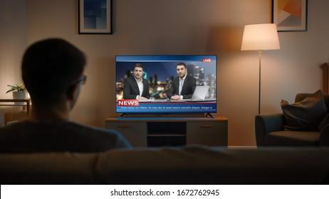 Hombre joven con gafas está sentado en un sofá y viendo la televisión con noticias en vivo. Es de noche y la habitación de la casa tiene lámparas que funcionan.