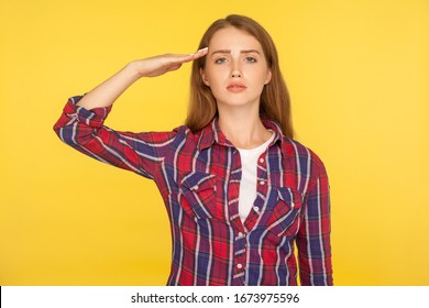 Yes, sir! Portrait of serious young ginger woman in checkered shirt saluting with respect and responsibility, patriotic citizen listening order with honor. studio shot isolated on yellow background
