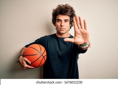 Junger hübscher Sportler, der Basketballball hält über lokalisiertem weißem Hintergrund mit offener Hand hält Stoppschild mit ernstem und selbstbewusstem Ausdruck, Verteidigungsgeste