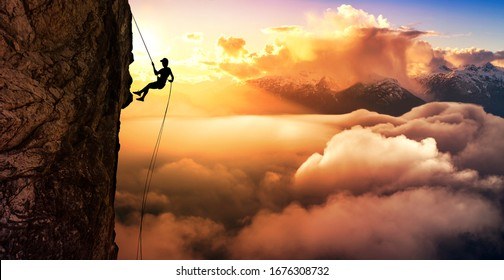Silhouette Abseilen von Cliff. Schöne Luftaufnahme der Berge während eines bunten und lebendigen Sonnenuntergangs oder Sonnenaufgangs. Landschaft aufgenommen in British Columbia, Kanada. zusammengesetzt. Konzept: Abenteuer