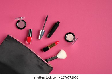 Makeup bag organizer with cosmetic products and professional make-up artist tools on pink background. Flat lay, top view. Beauty and fashion concept.