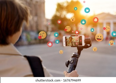 Teen girl blogger vlogger record vlog streaming video hold phone on selfie stick in urban city. Young female vlogger shoot social media blog on smartphone get likes emoji, over shoulder closeup view.