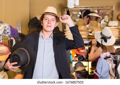 Porträt des lächelnden amerikanischen jungen Mannes versuchen auf Panama im Kopfbedeckungsgeschäft