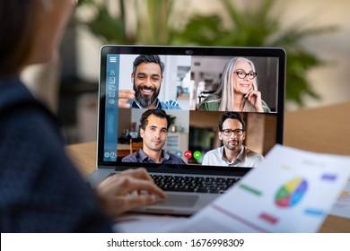 Rückansicht der Geschäftsfrau, die mit ihren Kollegen über Plan in Videokonferenz spricht. Multiethnisches Geschäftsteam, das einen Laptop für ein Online-Meeting in einem Videoanruf verwendet. Gruppe von Menschen klug von zu Hause aus arbeiten