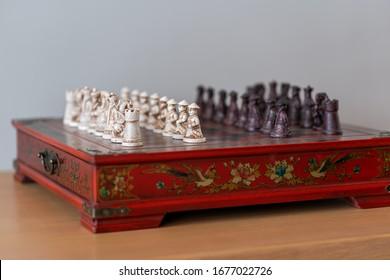 Wunderschönes chinesisches rotes Schach-Miniatur-Brettspiel der Armee aus kleinen Holzschnitzereien ist ein Strategie-Brettspiel für Spieler auf beiden Seiten. Sport, der das Gehirn nutzt und Meditation gut übt