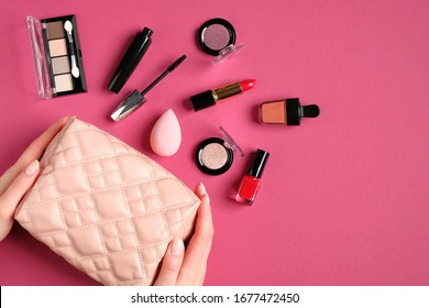Make-up cosmetic bag in female hands on pink background. Glamour makeup artist pouch with beauty products. Flat lay, top view