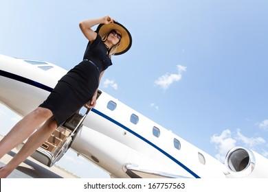 زاویه دید کم از زن با لباس ظریف ایستاده در مقابل جت شخصی در برابر آسمان