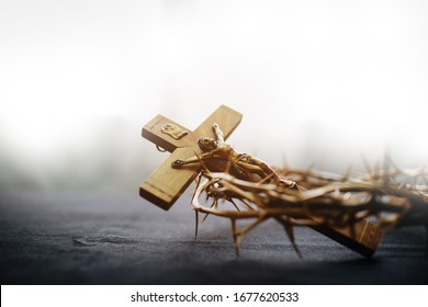 Close up of the crucifix of Jesus Christ and crown of throne on black background against window light, Easter concept with copy space