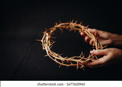 Close up of woman hand holding the  crown of throne on black background, Easter concept with copy space