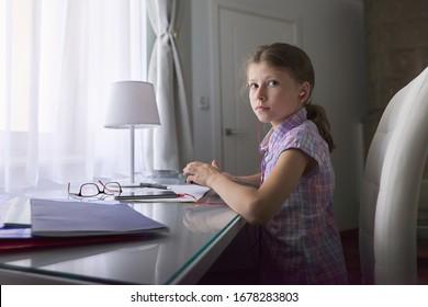 女児9、学校のノートブックとデジタルタブレット、耳にヘッドフォン、オーディオレッスン、教育技術を持つ窓の近くの机に自宅で座っている10歳