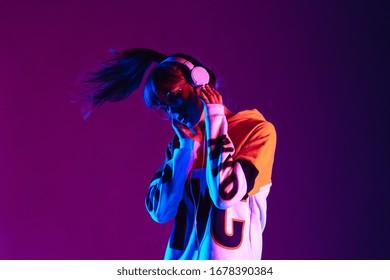 パーカーとヘッドフォンを身に着けているスタイリッシュなファッションティーンエイジャーモデルは、紫色のネオンライトで踊るdj音楽を聴いています。若い十代の少女は、バイオレットスタジオの背景でクールな音楽90年代のパーティーミックスをお楽しみください。スペースをコピーします。