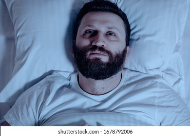 A lonely bearded man in bed at night cannot sleep, is unhappy and very tired. Sleep problems, stress, insomnia, bedroom, pajamas, white bedding.Close up