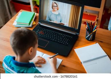 遠隔教育オンライン教育。男子生徒は家で勉強し、学校の宿題をします。ホーム遠隔教育。