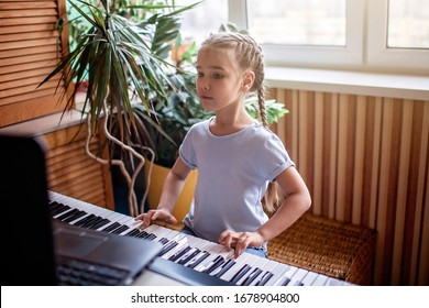 自宅でオンラインクラス中にクラシックなデジタルピアノを演奏するかなり若いミュージシャン、検疫中の社会的距離、自己隔離、オンライン教育の概念