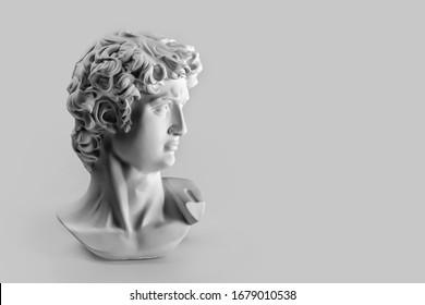 Estatua de yeso de la cabeza de David. Copia de yeso de la estatua del David de Miguel Ángel sobre fondo gris con copyspace para el texto. Escultura griega antigua, estatua del héroe