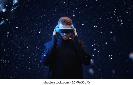 Young man in hoodie on virtual reality background. Guy using VR helmet. Augmented reality, future technology, game concept. Blue neon light.