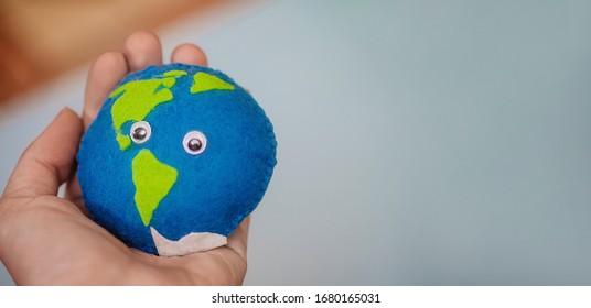 女性の手に地球。海と陸のフェルトで作られた自家製のおもちゃ。地球を救う。世界海の日、節水キャンペーン。Cosept Earth Day。