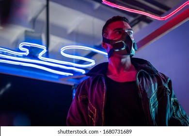 mixed race cyberpunk player in mask standing near neon lighting and looking away
