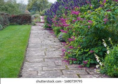 Een schilderachtige zomerse weergave van een stenen geplaveid pad door een prachtige tuin in Engelse stijl met bloemen in bloei