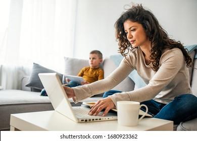 Glimlachende moeder die thuis met haar kind op de bank werkt tijdens het schrijven van een e-mail. Jonge vrouw die vanuit huis werkt, terwijl ze in quarantaine-isolatie was tijdens de gezondheidscrisis van Covid-19