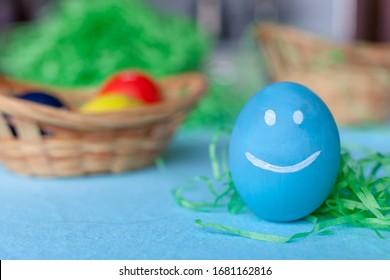 Закри пофарбовані блакитне яйце з пофарбованими очима та посмішками. На синьому фоні з копією простір. З Днем Великодня концепції.