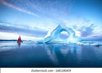 Velero con velas rojas navegando entre enormes icebergs durante el anochecer. Disko Bay, Groenlandia.