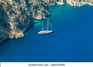 Amazing aerial view of Butterfly Valley in Fethiye Turkey. Summer landscape with mountains, green forest, azure water, sandy beach and blue sky in bright sunny day. Travel background. Top view. Nature