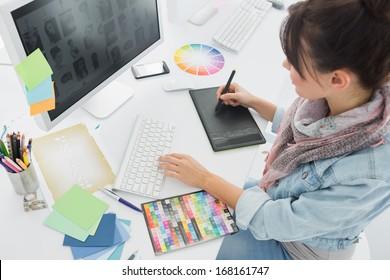 Hohe Winkelansicht eines Künstlers, der etwas auf Grafiktablett im Büro zeichnet