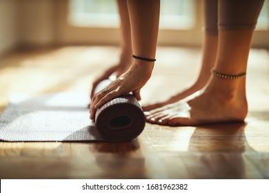 Close-up van de handen van een vrouw is oefeningsmat oprollen en voorbereiden op het doen van yoga. Ze traint thuis op de vloermat in de ochtendzon.