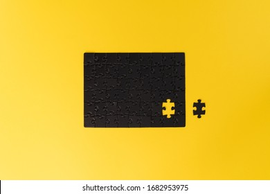 An unfinished black puzzle on a yellow background. The puzzle without one piece. Almost complete. Unfinished work concept