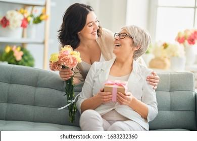 Gelukkige Moederdag! Mooie jonge vrouw en haar moeder met bloemen en giftdoos thuis.