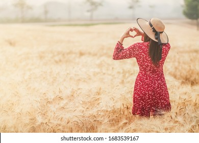 La mano de la doncella hizo un símbolo en forma de corazón sobre los campos de cebada dorada en la mañana para simbolizar la amistad, el amor y la compasión. Mostrando amor y amistad sobre los campos de cebada dorada