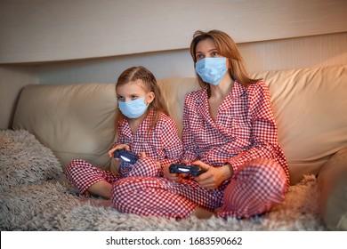 自宅の隔離自動検疫、covid-19でビデオゲームコントローラーとリビングルームのソファに座っているパジャマと医療保護マスクを身に着けている女性と少女。