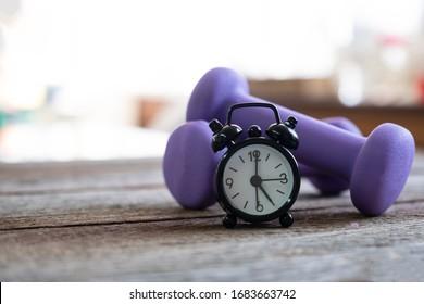 黒の目覚まし時計が夕方の運動時間に設定され、夕方の05時に木の床の2つの紫色の重りの横に15分が配置されています。コピースペースがあります