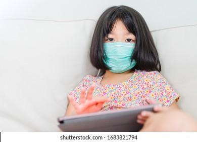 Covid-19コロナウイルス、在宅コンセプト。外科的保護マスクを身に着けている小さなアジアの中国人の女の子がウイルスから保護し、隔離されます。ウイルスの発生。Covid19コロナウイルスとパンデミックウイルスの症状。