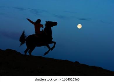 Luna llena natural y silueta de semental salvaje con jinete. Luz de luna de terror de fantasía con caballo encabritado sobre las patas traseras. Fondo de atmósfera de halloween de terror mágico.