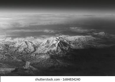 Blick aus dem Bullauge eines Flugzeugs auf die Berge. 10.000 Meter über dem Boden. Weißer schneebedeckter Berg während des Tages. Schwarzweiss-Foto.